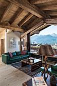Grünes Ledersofa am Fenster im Wohnzimmer im rustikalen Holzhaus