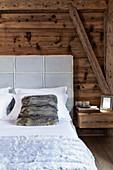 Bett mit gepolstertem Betthaupt und Fellkissen vor rustikaler Holzwand