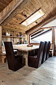 Dark leather chairs around dining table with corner bench in modern wooden house