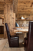 Dark leather chairs around dining table in modern wooden house