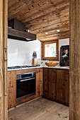 Modern fitted kitchen with rustic wooden cabinets and sloping ceiling