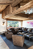 Velvet armchairs and leather sofa in living room of wooden house
