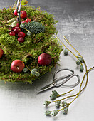 Festive DIY arrangement of moss, eucalyptus and apples on cake stand