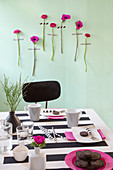Hot-pink flowers with stems stuck on green wall behind table set with black-and-white striped tablecloth