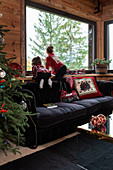 Mädchen auf schwarzem Polstersofa am Fenster in weihnachtlich dekoriertem Wohnzimmer eines Chalets