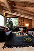Schwarze Polstermöbel und geschmückter Weihnachtsbaum im Wohnzimmer eines Chalets