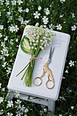 Posy of lily-of-the-valley and bird-shaped scissors on side table