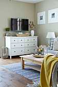 White sideboard and TV in autumnal, country-house-style living room