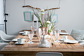 Wooden table set for Easter with ranunculus and white crockery