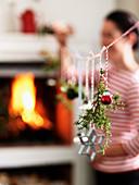 Weihnachtsdekoration aufgehängt an Schnurr vorm Kamin