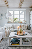 Autumn arrangement on coffee table in bright, shabby-chic living room