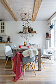 Autumnal decorations in dining area with wooden table and shell chairs