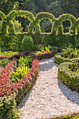Knot garden with gravel path and artistically cut hedge