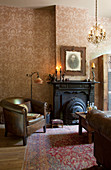 Vintage leather armchairs in front of black fireplace in living room of period building with patterned wallpaper