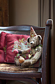 Scatter cushions and teddy bear on vintage leather couch