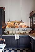 Küchenzeile übereck, darüber Pendelleuchten in Altbau-Küche mit Schachbrettboden