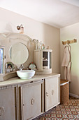 Vintage washstand with integrated mirror and cupboards in top section in bathroom