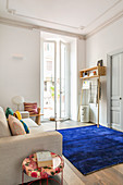 Dark blue rug providing a splash of colour in white living room of period apartment