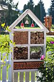 House-shaped bug hotel on garden fence