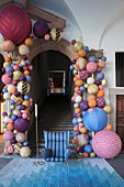 Blue armchair on rug at foot of historic stairs with arched doorway decorated with multicoloured fabric balls