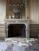 Modern, geometric tiles on antique mosaic floor in front of fireplace