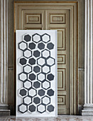 Modern, grey-and-white tiles on panel against antique door