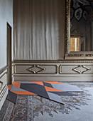 Modern, geometric tiles on antique mosaic floor