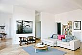 Pale sofa in modern open-plan interior with herringbone parquet floor