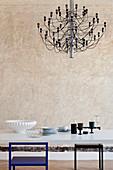 Moderner Kronleuchter überm Esstisch vor Wand mit Patina