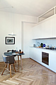 Dining table in small kitchen-dining room with kitchen counter and herringbone parquet floor