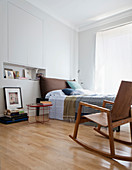 Modern rocking chair next to bed in bedroom with fitted wall cupboards