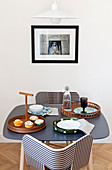 Black-and-white striped chairs at small table below picture on wall