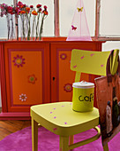Furniture in bold colours: neon green chair in front of red and orange cabinet