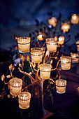 Glass tealight holders on tree-shaped frame decorating table