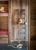 Ladder leaning against rustic wooden wall made from reclaimed wood next to bunk beds