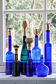 Blue glass bottles with decorative stoppers on windowsill