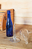 Broken crystal glass and blue bottle to be recycled as vase