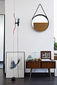 Round mirror above retro sideboard with vintage-style accessories