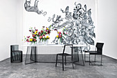 Delicate dining table and black chairs in front of exotic wallpaper