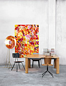 Various chairs around wooden table in front of abstract painting