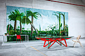 Red and green designer table in front of huge painting of jungle