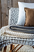 Stack of knitted blankets and cushions in natural shades