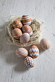 Brown hens' eggs painted with white patterns in Easter nest made from raffia and Iceland moss