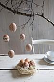 Bemalte Hühnereier als Osterdeko in Nest und an Zweigen aufgehängt