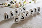 Weiße Eier beschriftet mit 'Happy Easter' als Osterdekoration