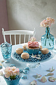 Cupcake and macarons on table set in pale blue and pink