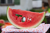 Slice of watermelon with name cut out through middle