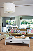 Sofa and coffee table on sisal rug in cosy living room with glass wall overlooking garden