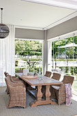 Massive wooden table and wicker chairs next to glass wall with folding glass doors and view of garden