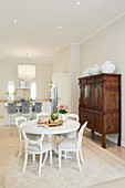 Round white dining table and antique-style upholstered chairs with kitchen counter in background